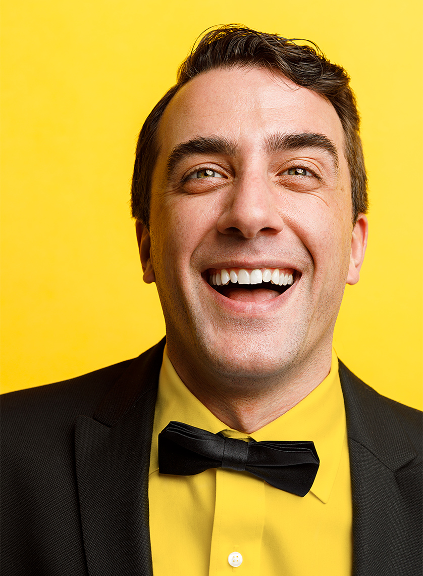 Man wearing a tuxedo and laughing.